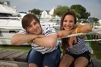 Happy couple sitting on pier