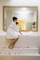 Woman sitting next to bubble bath
