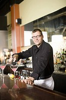 Male bartender pouring cocktail