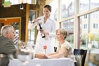 Waitress opening wine for couple