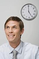 Businessman next to wall clock