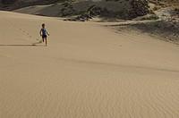 Person running down sand dune