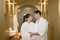 Couple in bathrobes smiling at each other