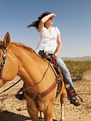 Hispanic woman riding horse