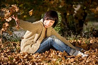 Germany, Bavaria, Young woman throwing autumn leaves, portrait