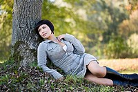 Germany, Bavaria, Young woman leaning on tree