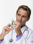 Male Doctor preparing syringe, portrait
