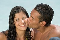 Hispanic man kissing girlfriend on cheek