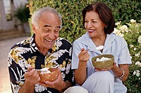 Senior Hispanic couple eating ice cream