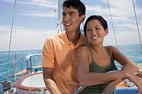 Multi-ethnic couple steering sailboat