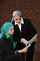 Middle Eastern businesswomen looking at newspaper