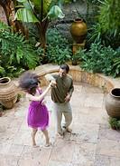 Multi-ethnic couple dancing on patio