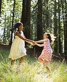 Multi-ethnic girls dancing in woods