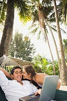 Asian man with laptop in hammock