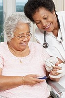 Doctor testing African American woman's blood sugar