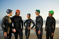 Multi-ethnic swimmers wearing wetsuits and goggles