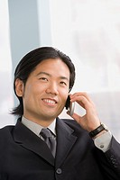 Asian businessman talking on cell phone