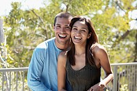 Multi-ethnic couple laughing outdoors