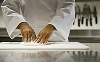 African male chef kneading dough