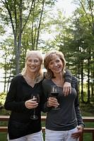 Women standing on deck drinking red wine