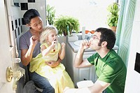 Fathers teaching daughter to brush teeth