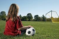 Girl sitting in soccer field