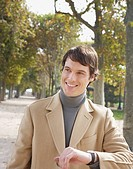 Businessman outdoors in park checking the time