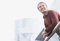 Businessman on balcony holding folders