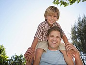 Man giving young boy shoulder ride outdoors at park