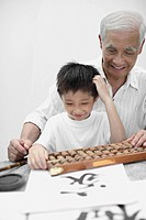 Man and young boy indoors at table with abacus
