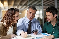 Three businesspeople in office with paperwork