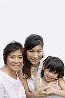 Two women and young girl indoors bonding