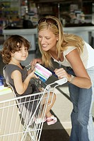 Woman and young girl in doorway of grocery store with shopping cart