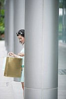 Woman outdoors by large pillar looking in shopping bag
