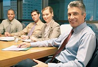 Four businesspeople in a boardroom looking at camera