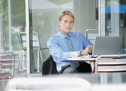Businessman at outdoor patio table with laptop