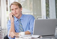 Businessman on cellular phone at outdoor patio table