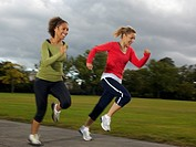 Two women running on a path in a park