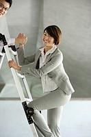 Businessman helping businesswoman up ladder in structure