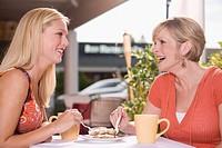 Two women at a street café sharing a piece of tiramisu