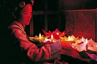 NAXI WOMAN LIGHTING CANDLE LANTERNS MEANT TO BE FLOATED DOWN THE CANALS, LIJIANG, CHINA