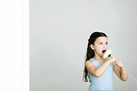 Little girl singing into flower, looking away