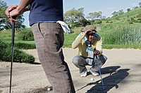 Cropped view of two people on a golf course