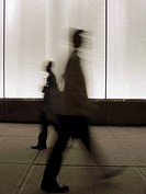 Commuters walk past lighted building in New York, New York, USA