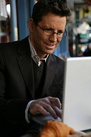 Mature man typing on a laptop outdoors