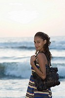 Portrait of a young woman standing on the beach and carrying a hand bag