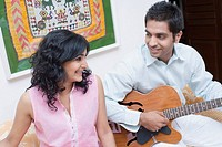 Young man playing the guitar with a young woman sitting beside him