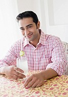 Portrait of a young man holding a glass of lemon juice and smiling