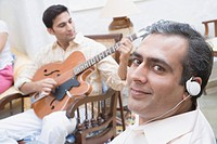 Portrait of a mid adult man wearing headphones and a young man playing guitar in front of him