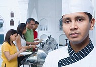 Portrait of a chef with two mid adult couples having lunch in the background